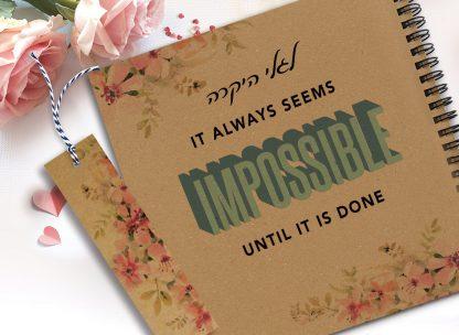 מחברת מעוצבת עם שם ומשפט השראה: ״It always seems impossible until it's done״